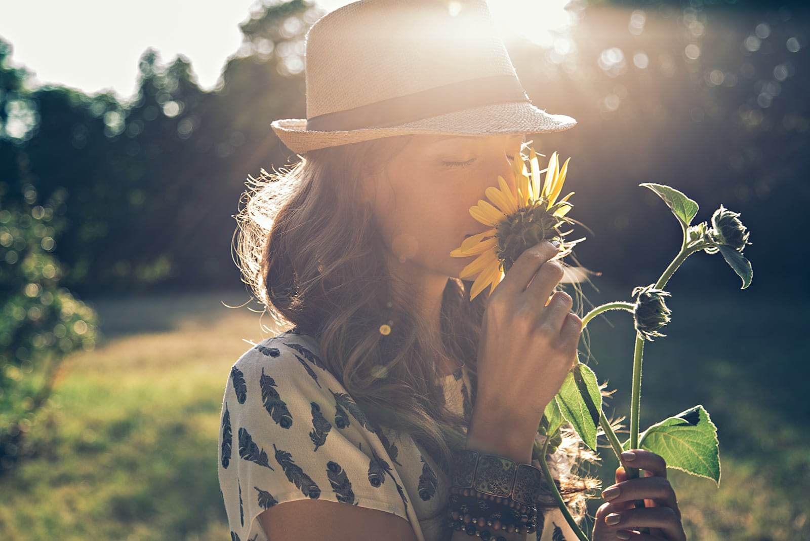woman in nature smelling sunflower