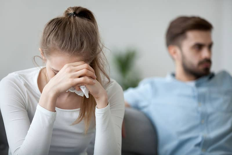 young woman crying while man sitting