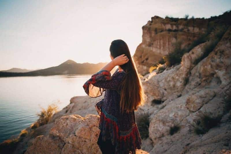 woman touches her hair in front of sea