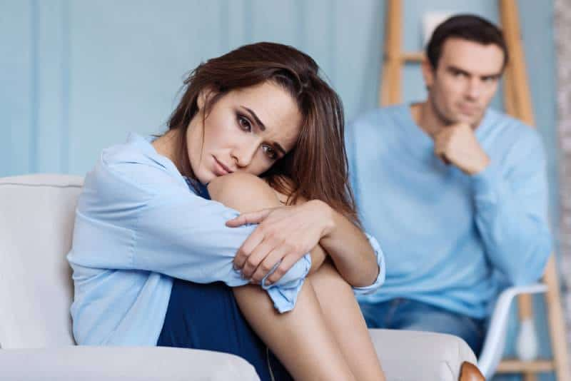 Upset young woman sitting at home next to his husband