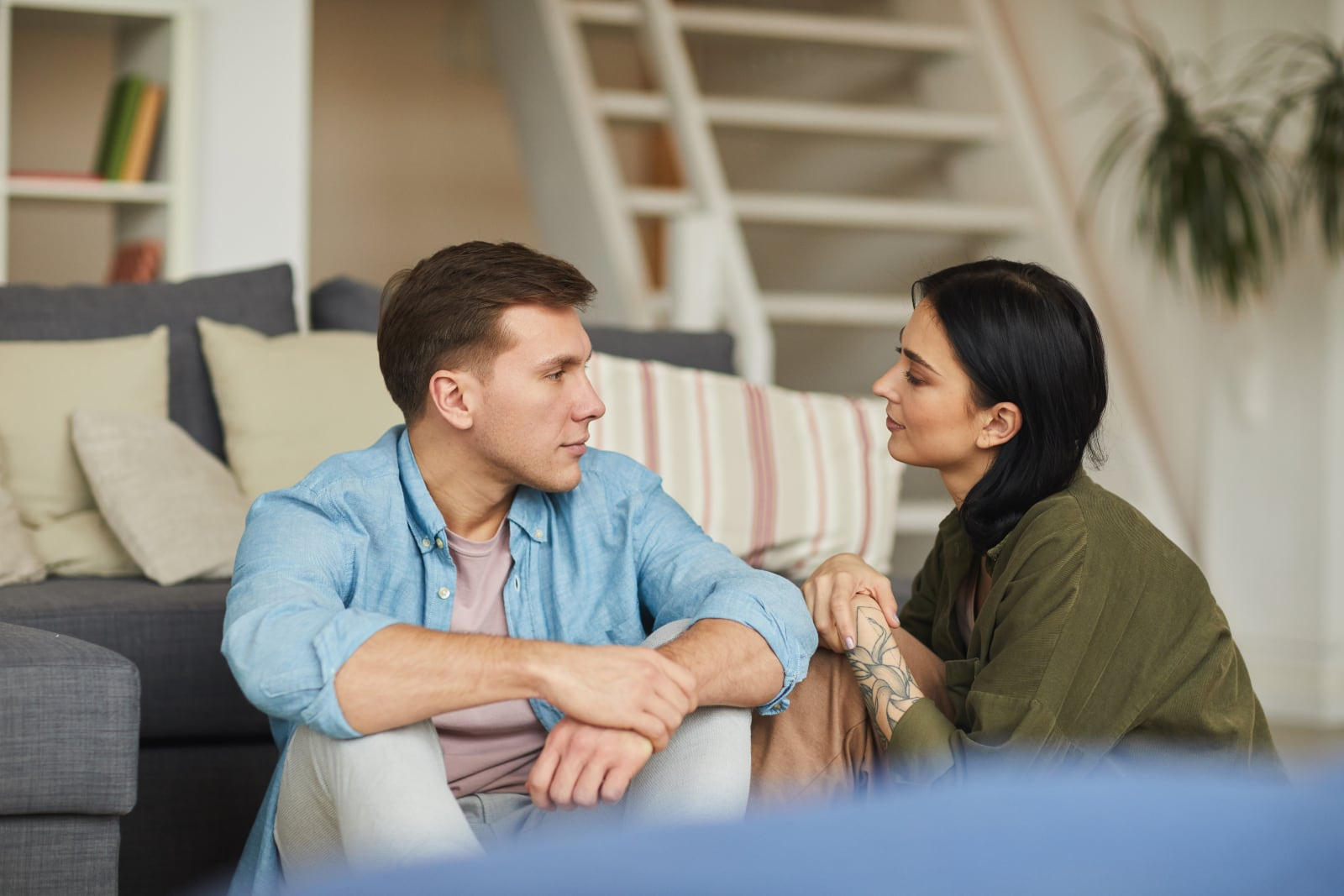 a couple talking while sitting on the living room floor