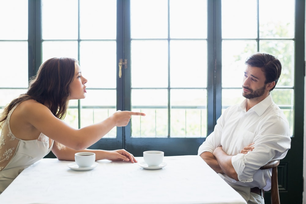 a man and a woman are sitting at the table arguing