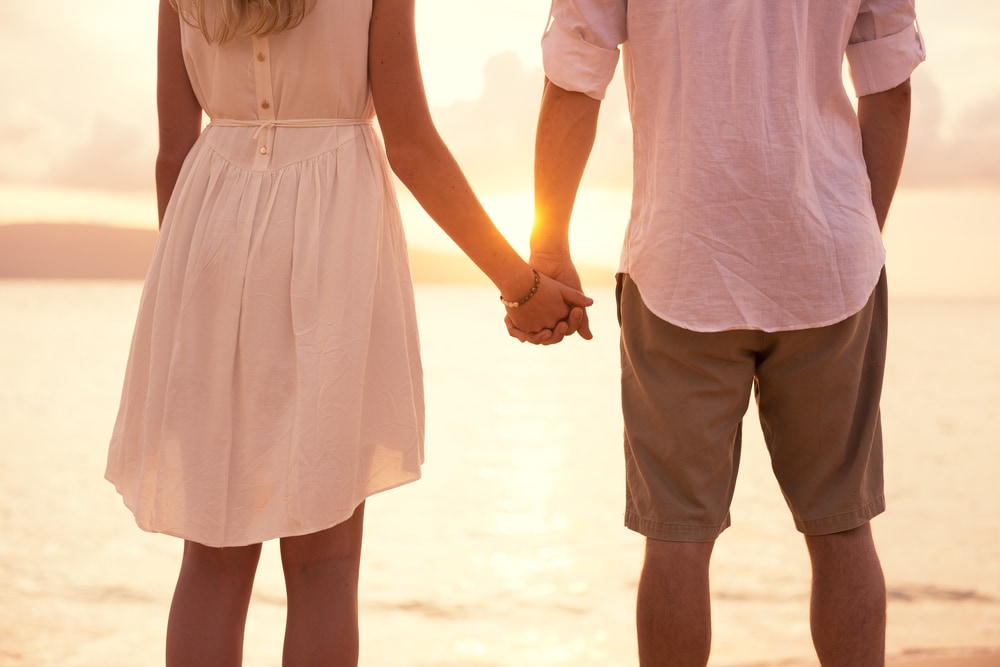 a man and a woman are walking along the beach holding hands