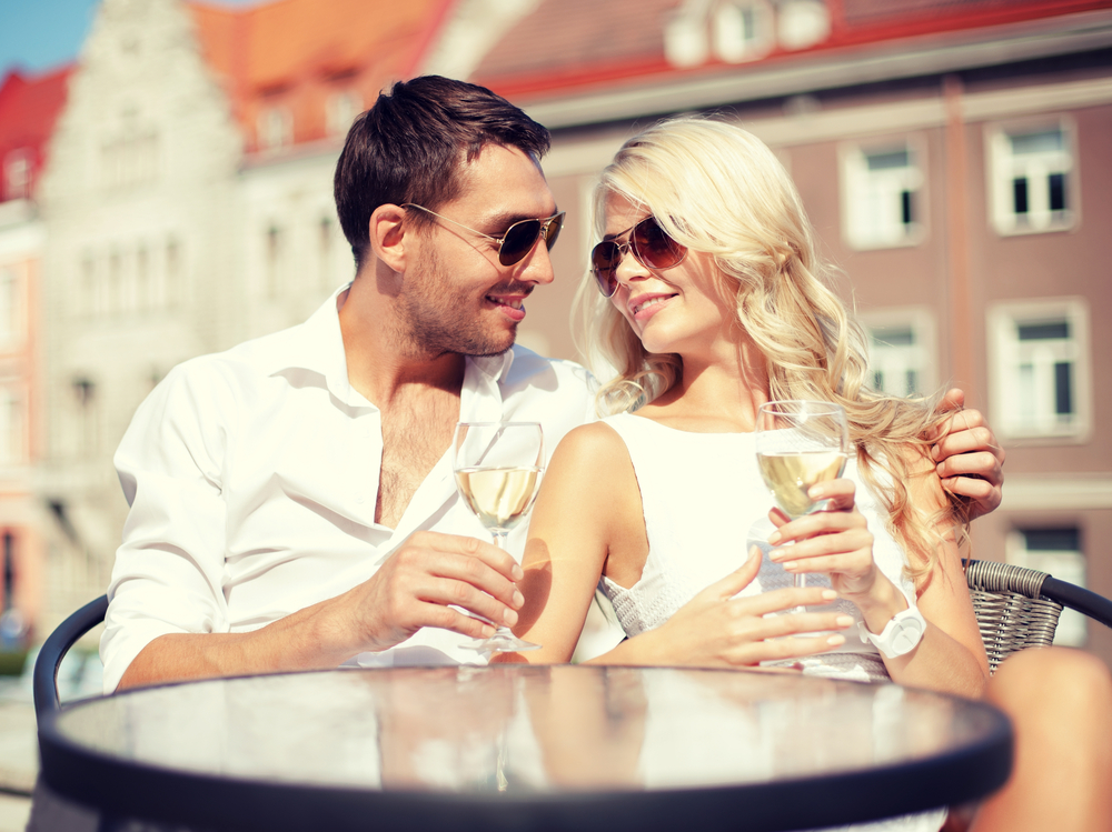 a man and a woman sit drinking wine