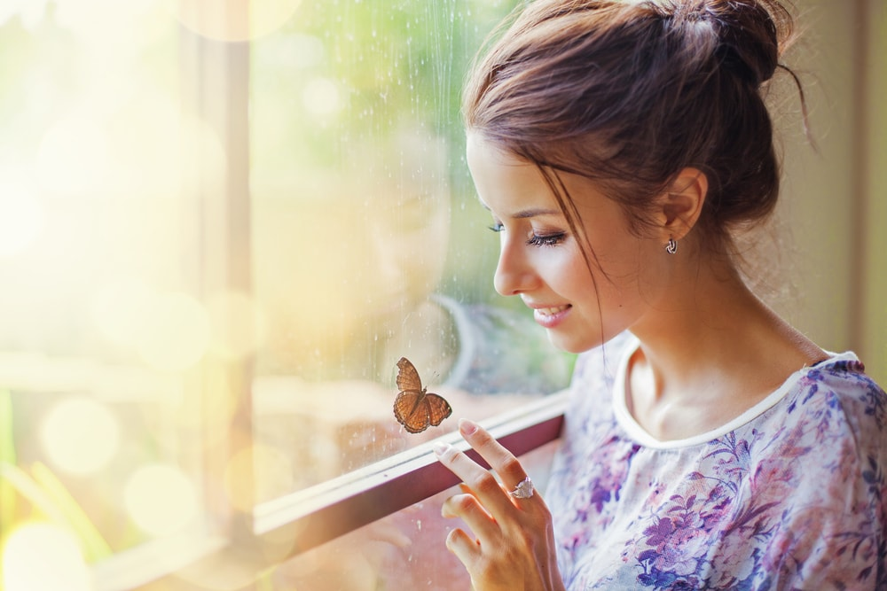 a smiling brunette stands by the window and touches a butterfly