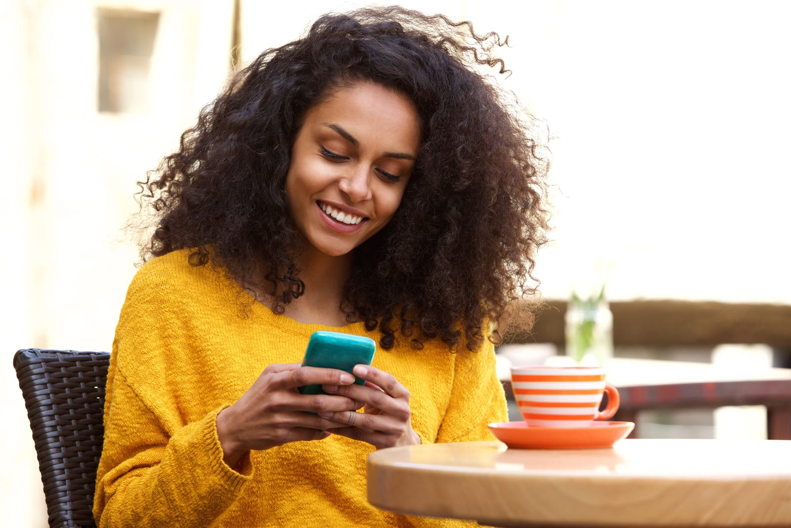 a smiling happy black woman in a yellow sweater sits drinking coffee and texting