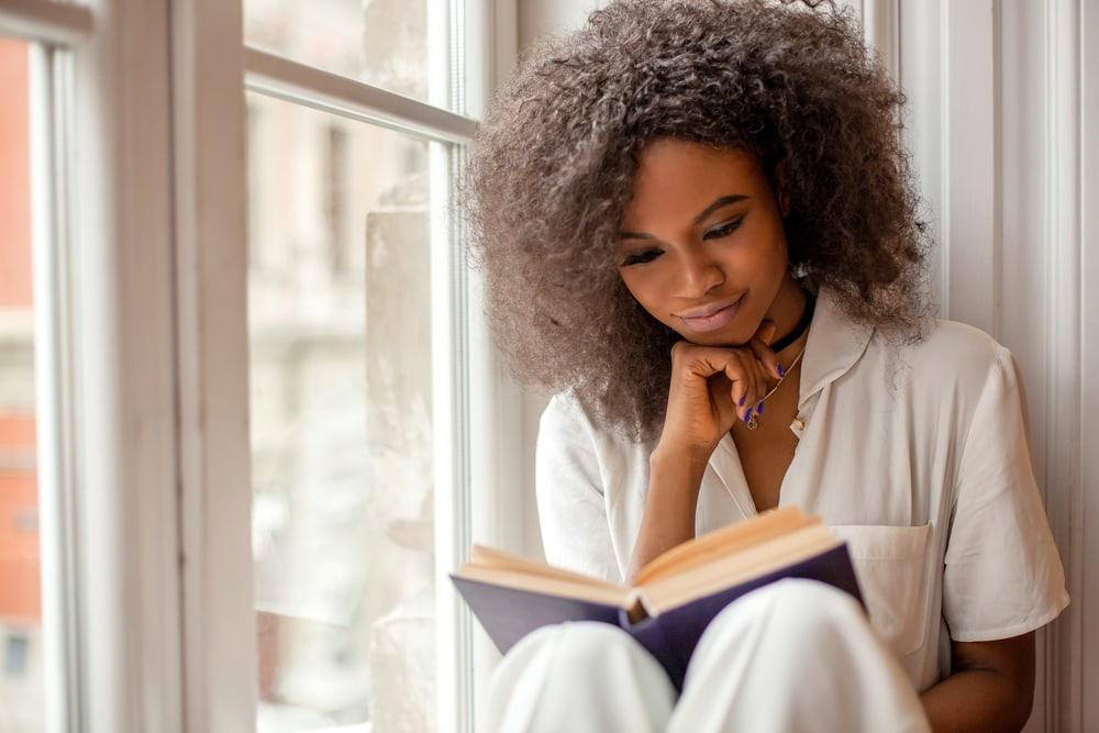 a woman sits by the window and reads a book