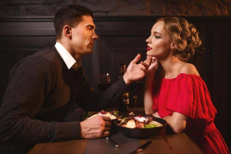 attractive couple looking each other at restaurant