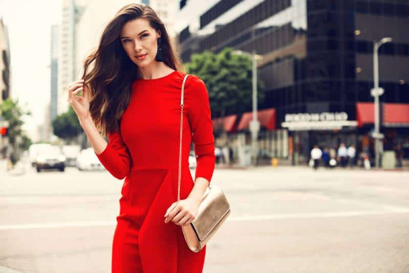 brunette woman wearing red dress, golden purse outside on the street