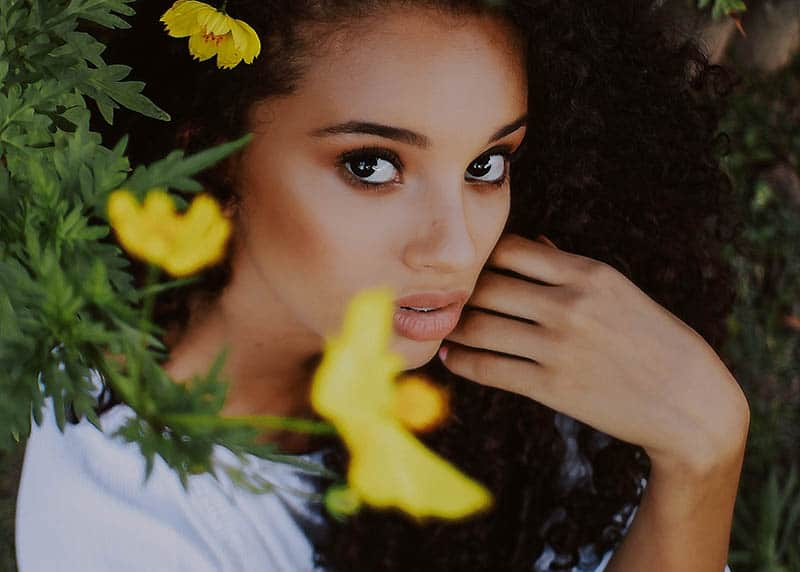 Curly woman behind flowers