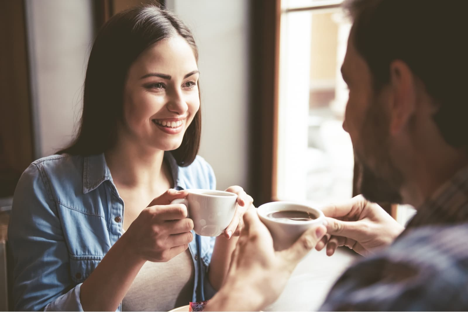 couple holding cups of coffee and talking