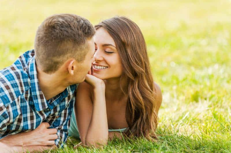 couple lying on the grass while looking at each other