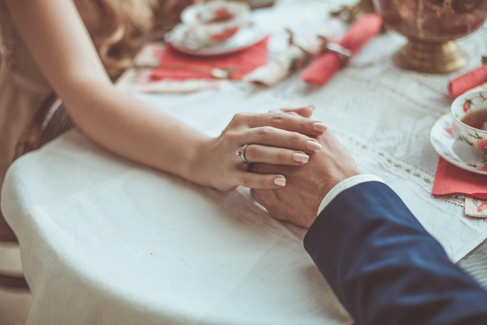 couple holding hands while sitting at the table