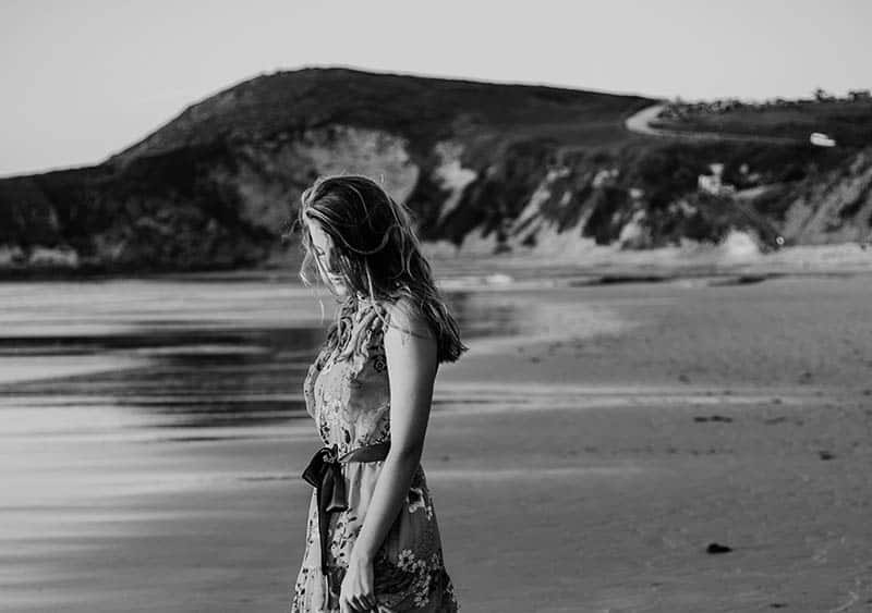 Sad woman in dress walking on beach