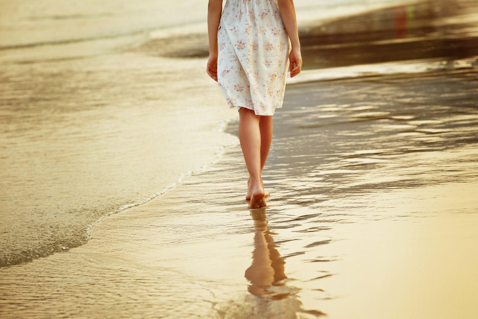 lonely girl is walking along island coastline