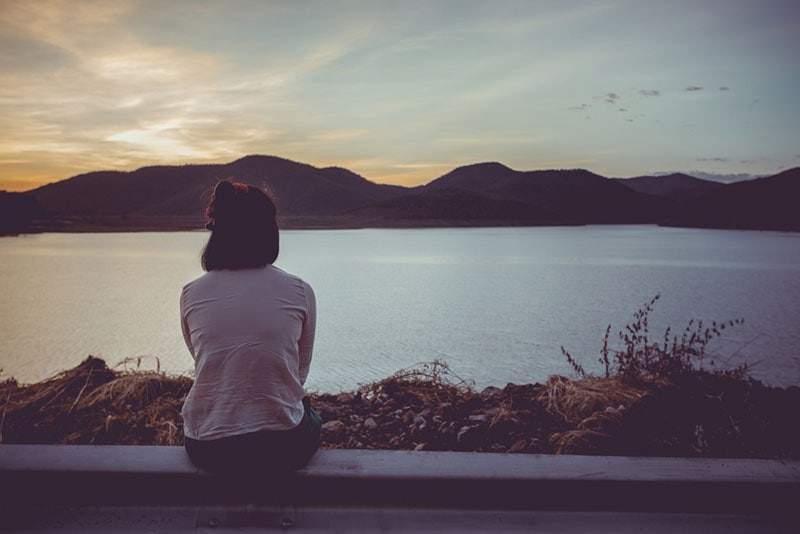 lonely woman looking at lake