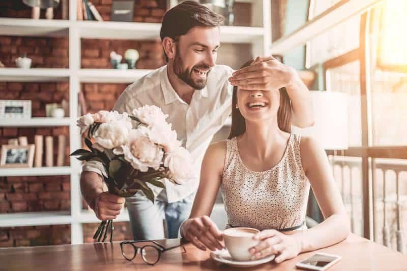 man is presenting flowers to his girlfriend