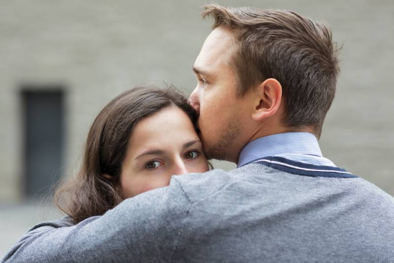 man kissing her worried girlfriend outside