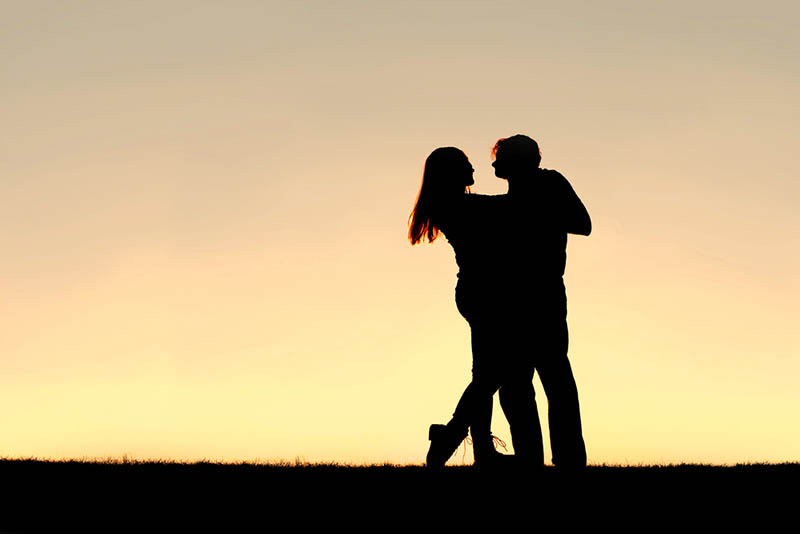 silhouette of couple dancing outside