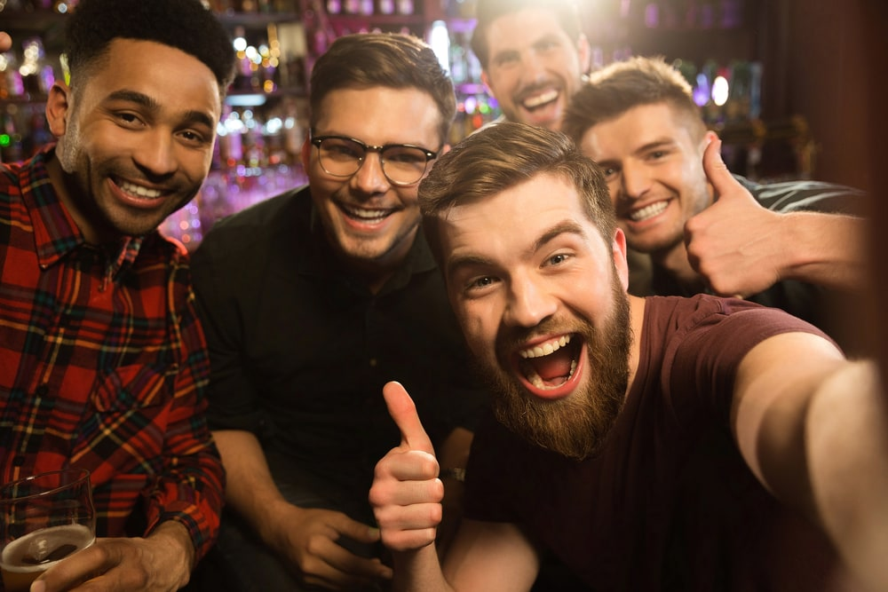 smiling friends at the bar take a selfie photo
