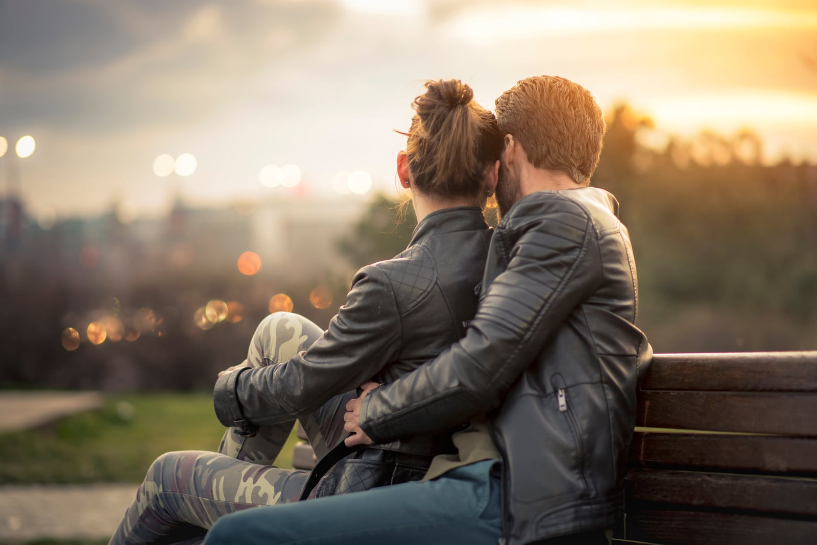 sweet couple embraced on a bench in park