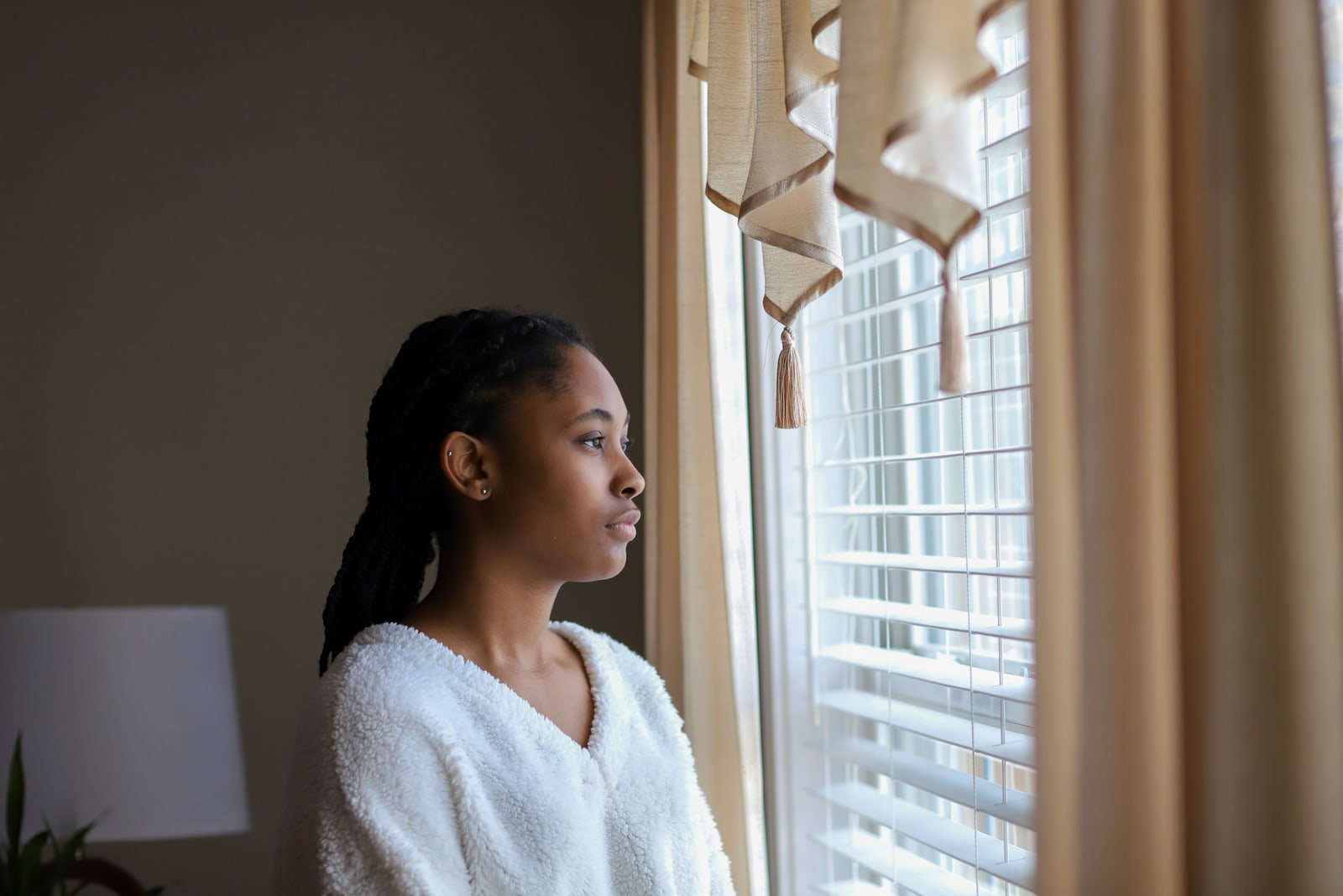 teenaged girl looking out a window and feeling sad