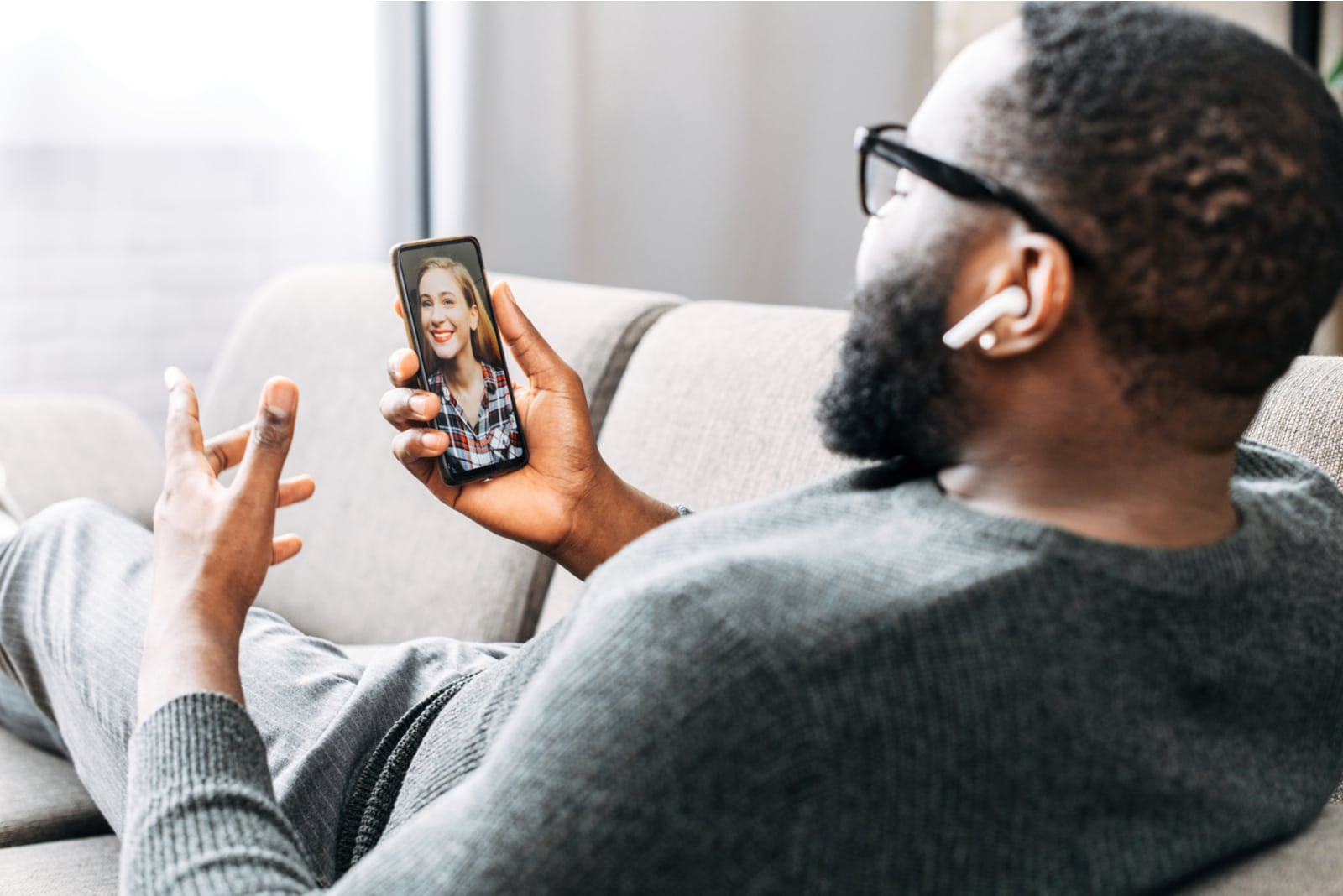 the black man sits on the couch and talks to the smiling blonde over a video call