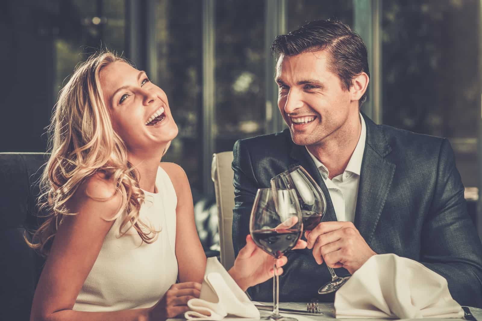 the man and woman at dinner laugh