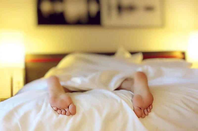 person's feet on bed