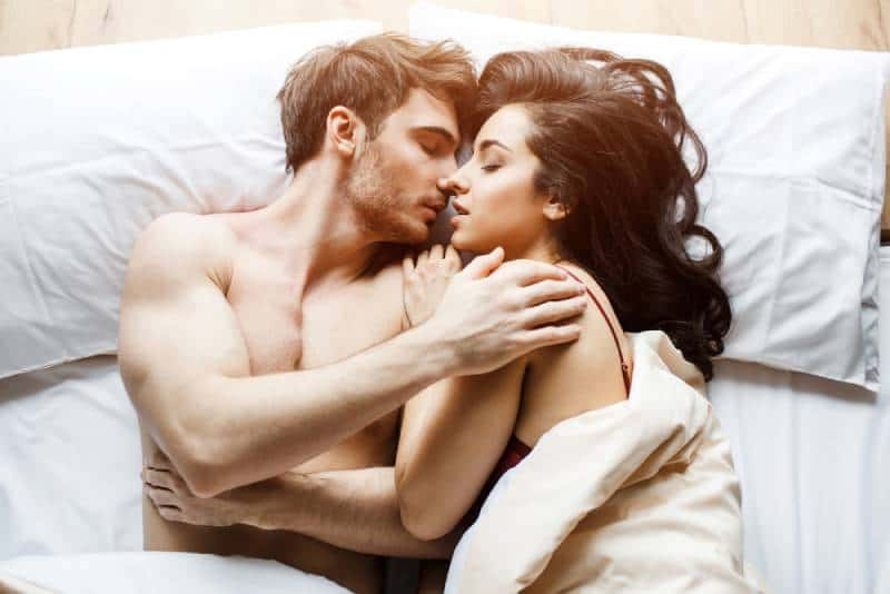 romantic couple kisses while lying on bed