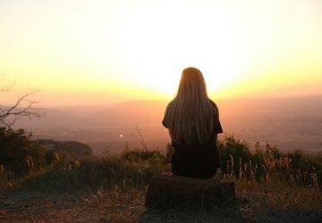 back view of woman sitting on mountain watching sunset