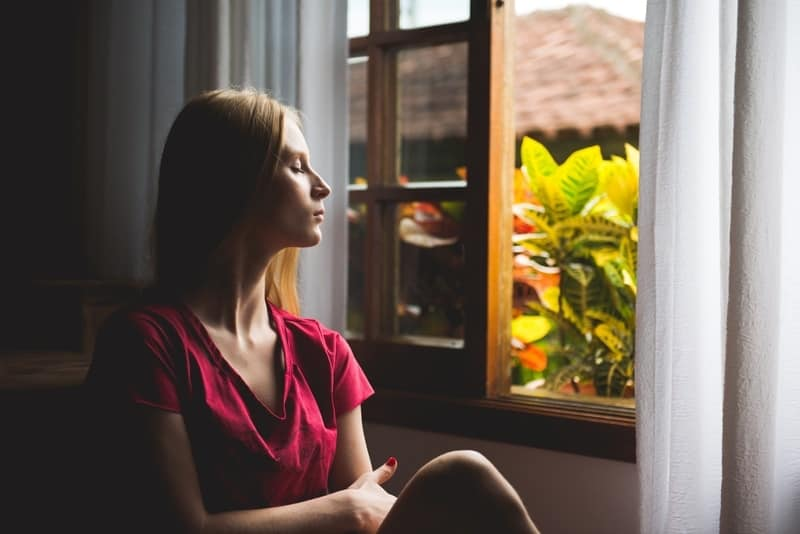 Woman sitting by the window meditating