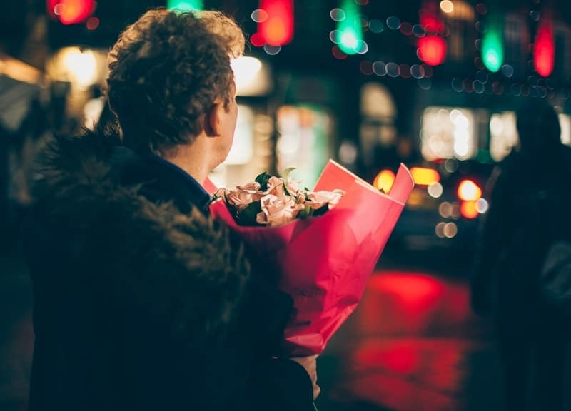 Man waiting on street with a bouquet of flowers