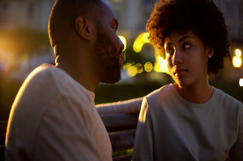 a loving couple sitting on a bench at dusk and talking