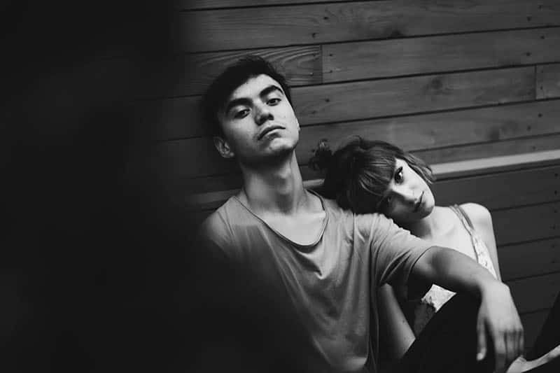 Young woman leaning on man's shoulder