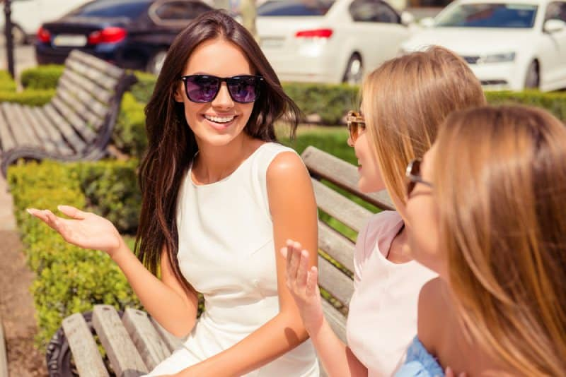 cheerful woman talking to her friends at bench in park