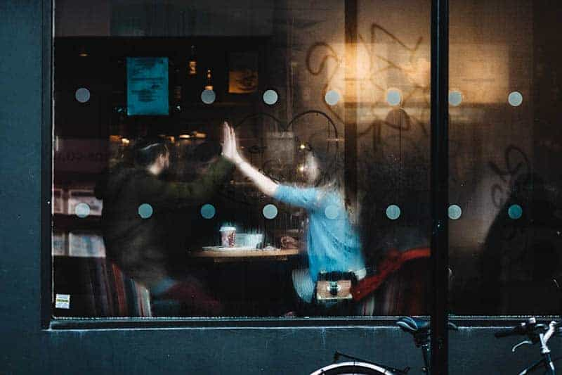 man and woman high five in cafe