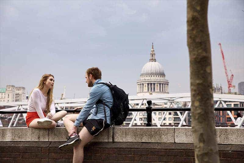 man and woman sitting outside and talking