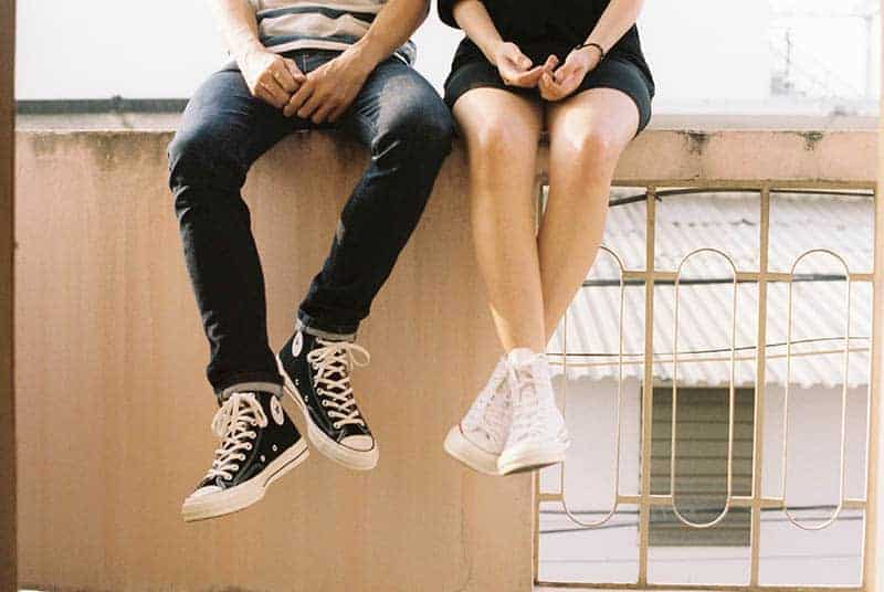 man and woman wearing converse all star sitting beside each other