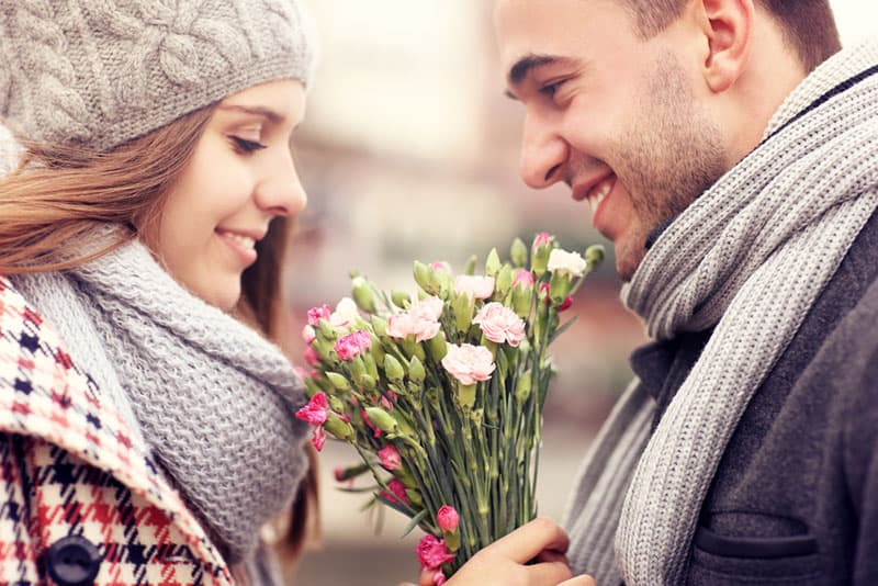 man giving flowers to the woman