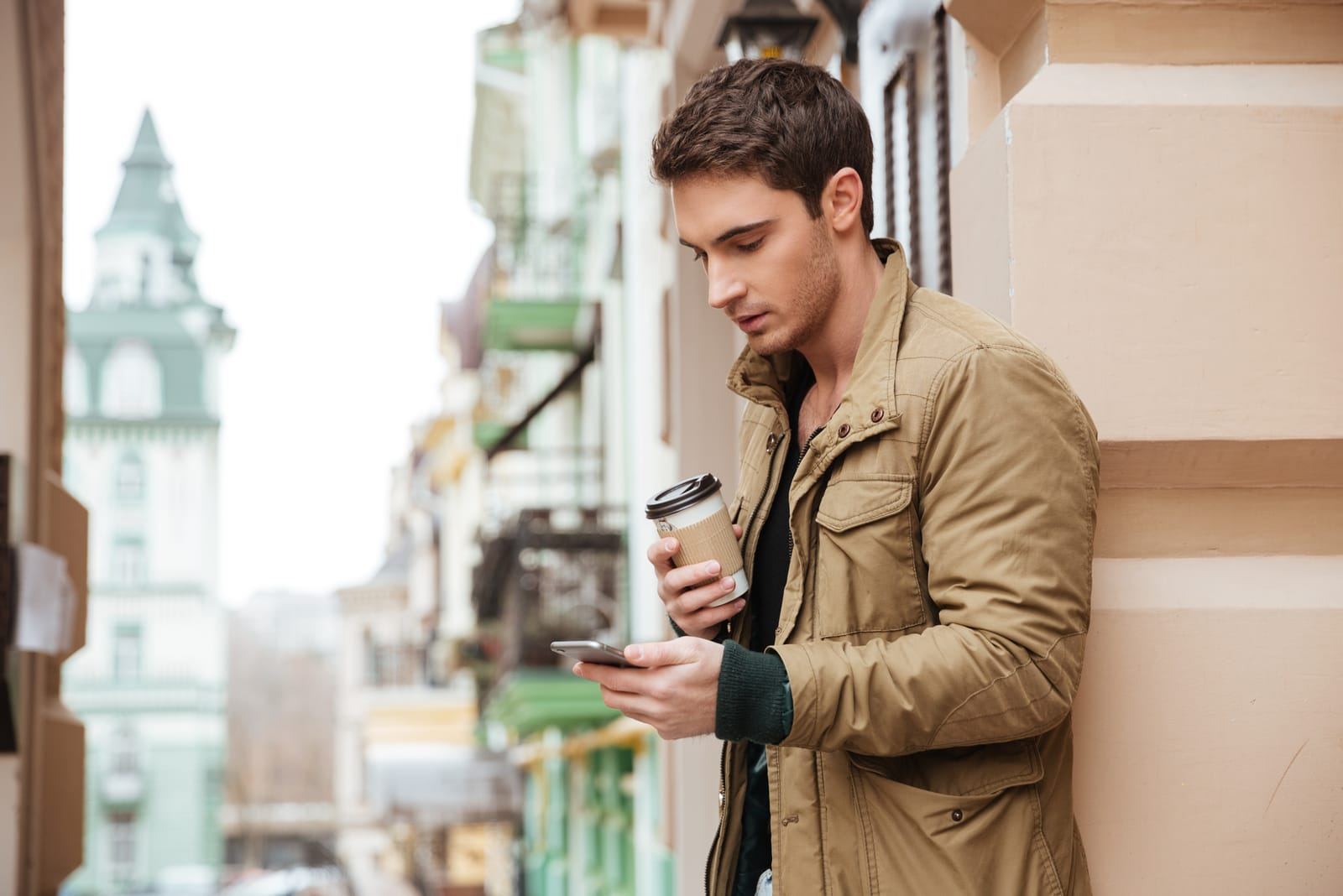 man holding cup of coffee and phone in his hands