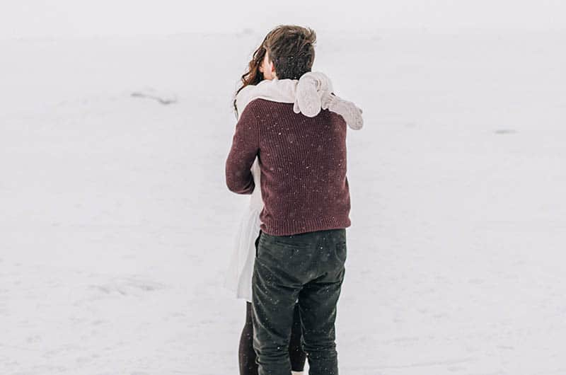 Couple hugging and kissing on snow