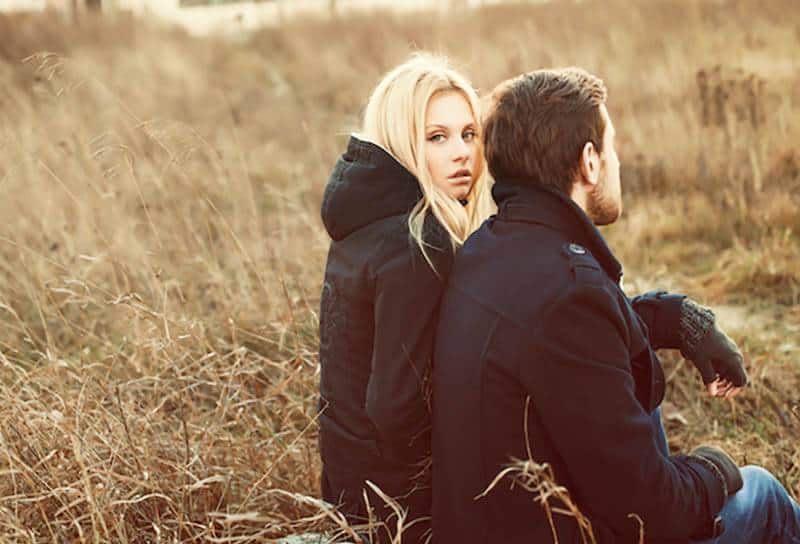 thoughtful blonde woman sitting next to man wearing black jacket and gloves outside