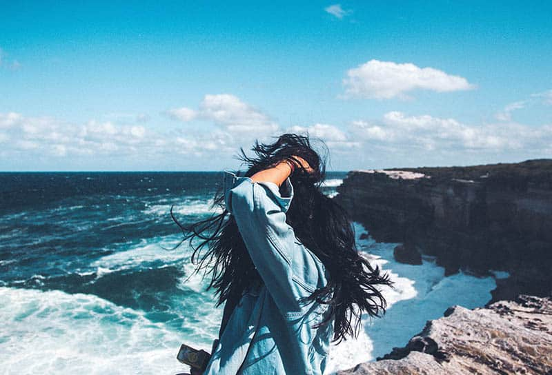 woman holds hair and stands in front of sea