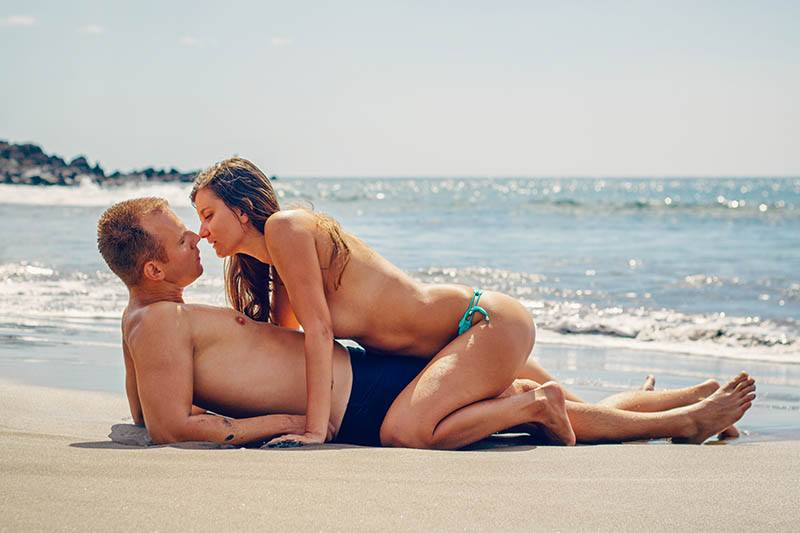 woman in biking sits on man and kisses him while he lying on the beach