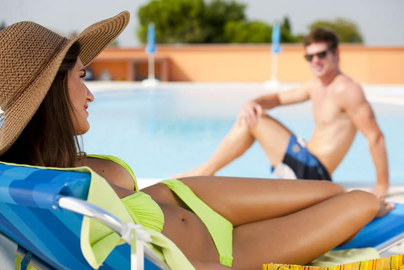 woman in swimsuit flirting with man on the pool
