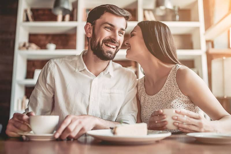 woman whispering on man ear