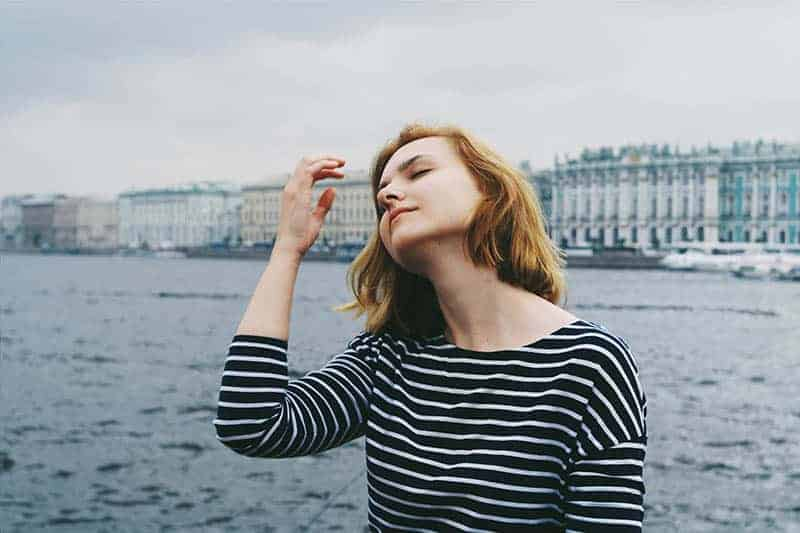woman with closed eyes standing against the sea