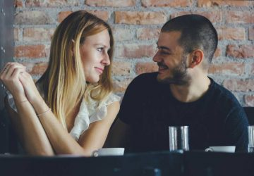 A young man and woman flirting during a date. Couple sitting in cafe