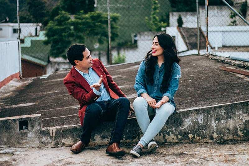 smiling man and woman sitting outside and talking